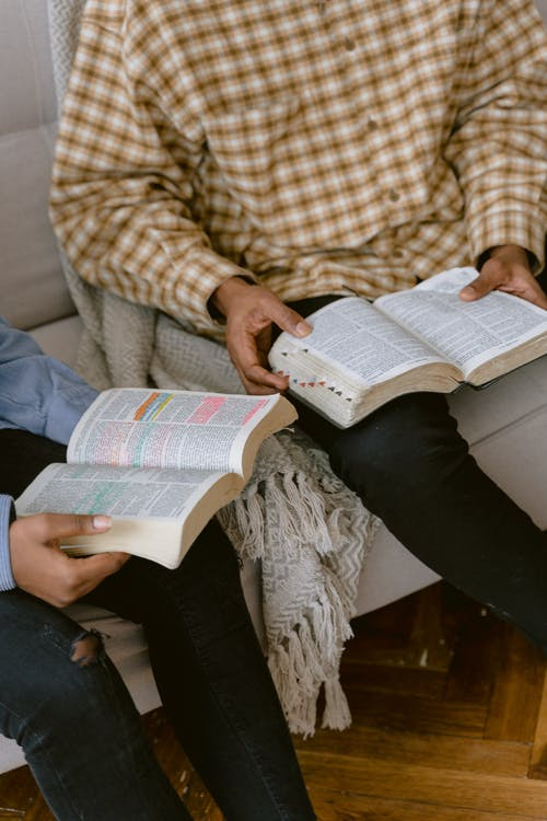 Two People Reading Bible while Sitting on a Sofa