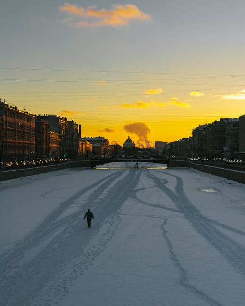 Snowy frozen channel with person walking at sunset