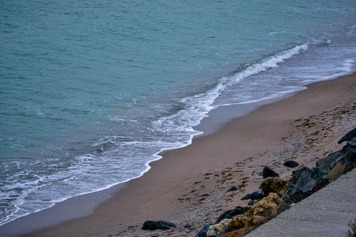 Picturesque seascape of sandy beach with rocks placed near blue wavy sea in daytime