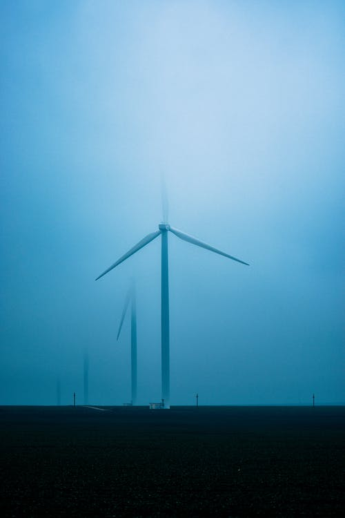 High windmills placed in field in countryside