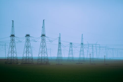 Electric towers in countryside field under blue sky