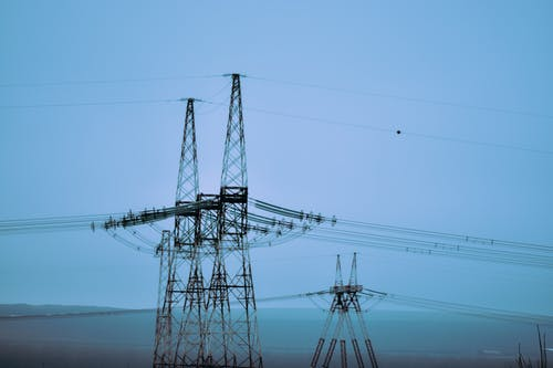 Transmission towers against endless sea and mount