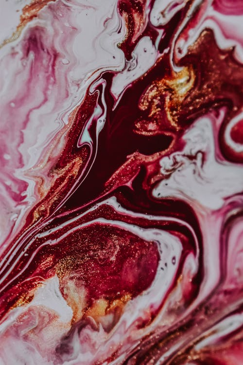 Overhead view of abstract background representing artwork with multicolored wavy dye fluids and glittering particles