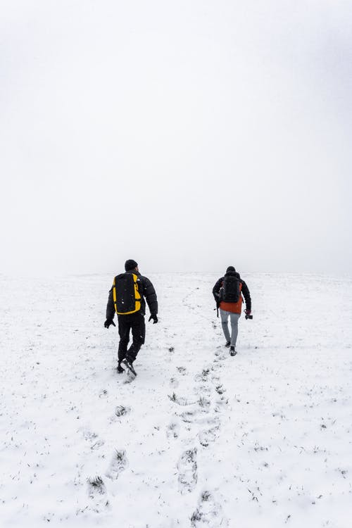 Men Walking on Snow Covered Field