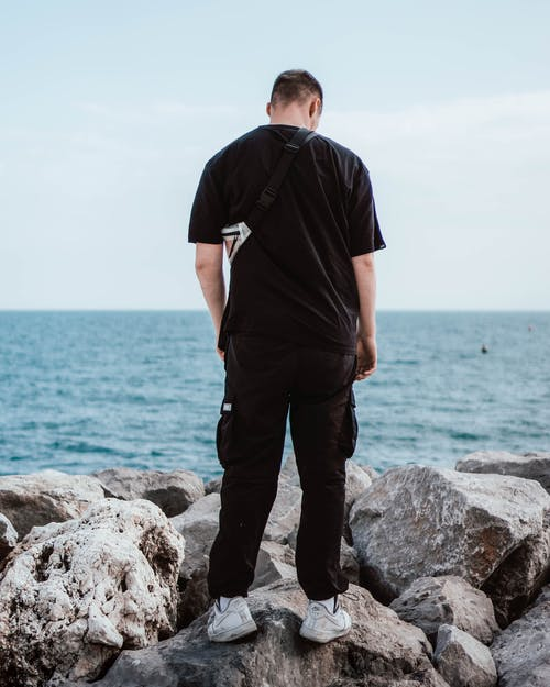 Man in Black T-shirt and Black Pants Standing on Rocky Coast