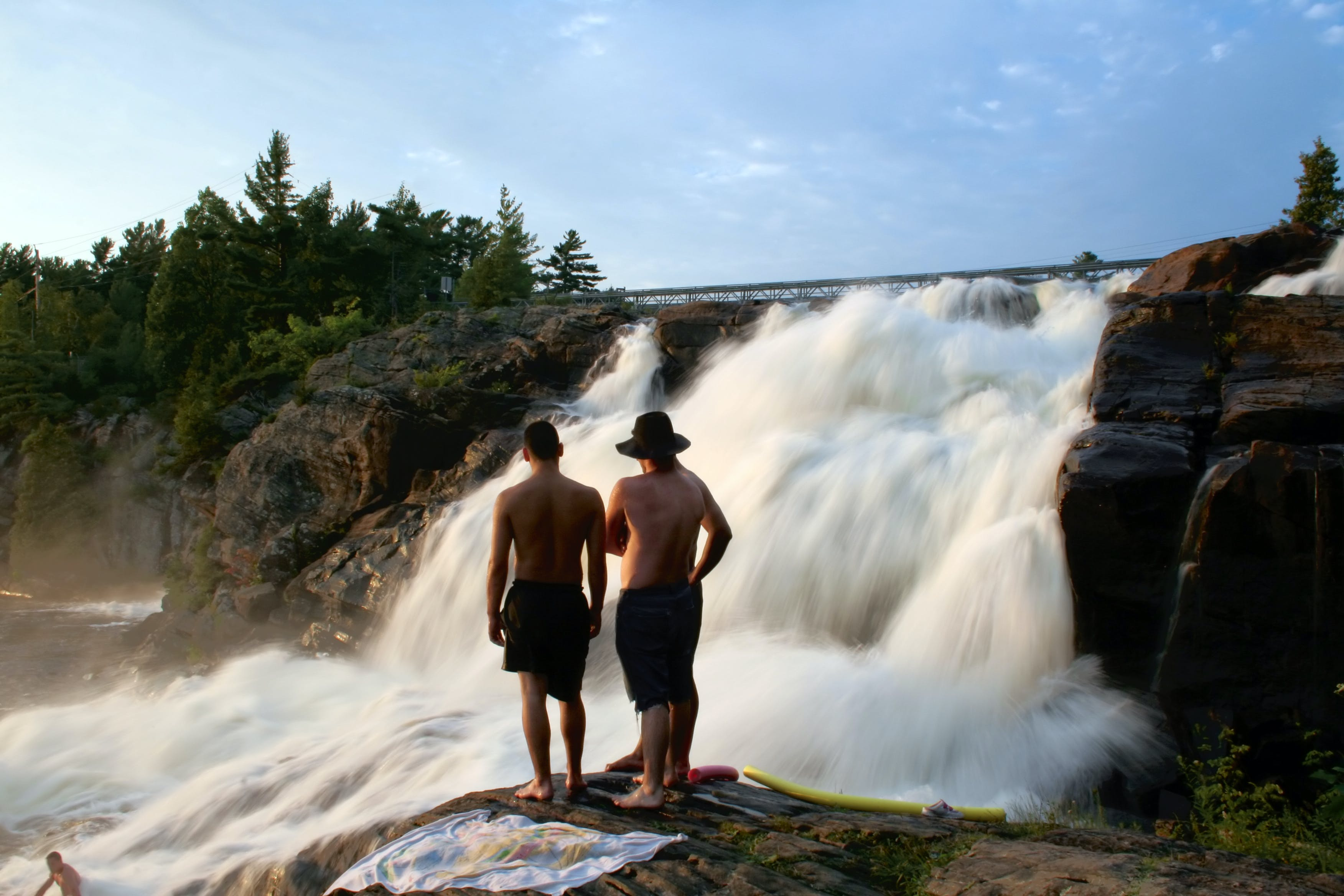Three Person Standing on Rock Watching Waterfall