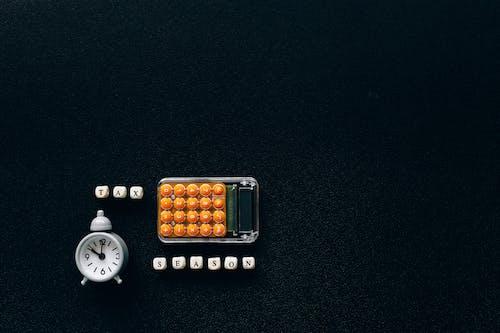 Tax Season Words Near Clock and Calculator