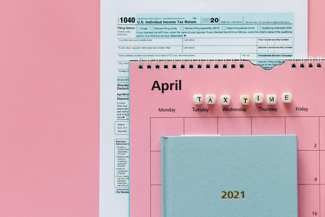 Tax Return Form and 2021 Planner on Pink Surface