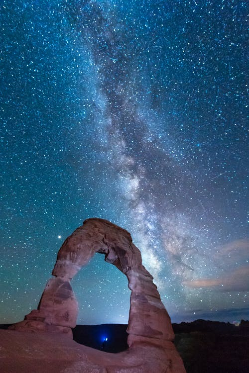 Man in Black Jacket and Pants Standing on Rock Formation Under Starry Night