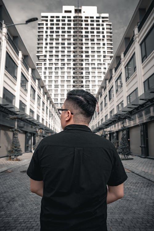 Man in Black Polo Shirt Standing on Sidewalk
