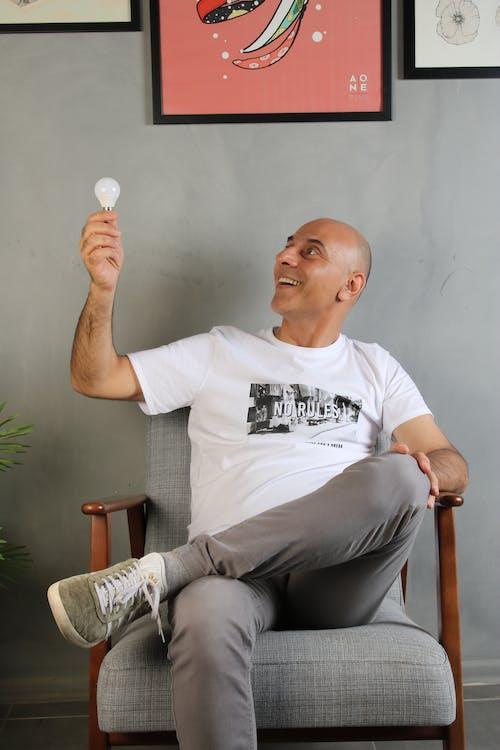 Man in White Crew Neck T-shirt Sitting on Brown Wooden Armchair