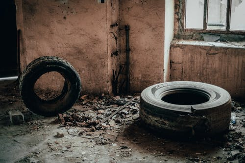 Weathered tires on dirty floor near shabby wall with peeling plaster and old window in abandoned building with rubbish and ruins