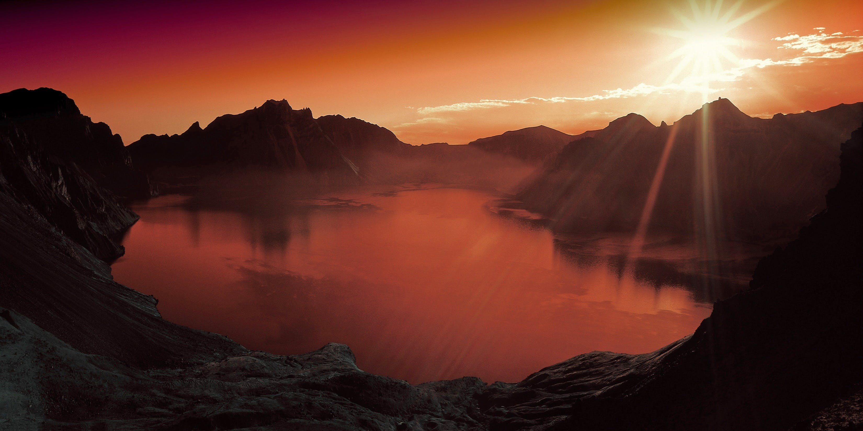 Body of Water Surrounded by Mountains during Sun Set