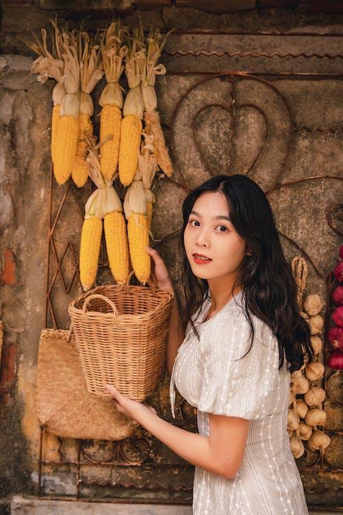 Girl in White Shirt Standing Beside Corn