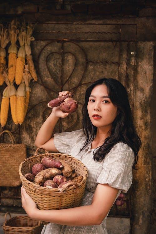 Woman in Gray Long Sleeve Shirt Sitting Beside Brown Wicker Basket With Corn