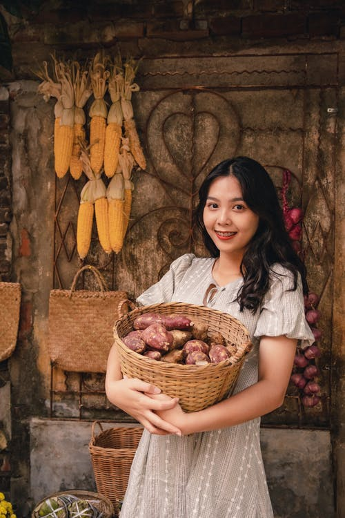 Girl in White Shirt Holding Brown Woven Basket With Yellow Banana Fruits