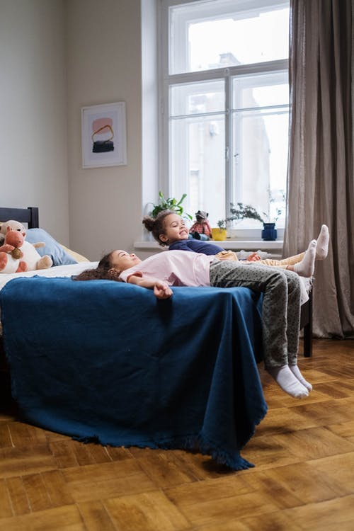 Kids Lying on Bed Covered With Blue Blanket