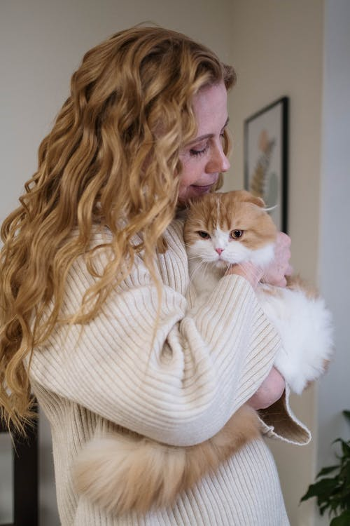 Woman in White Knit Sweater Holding White and Orange Cat