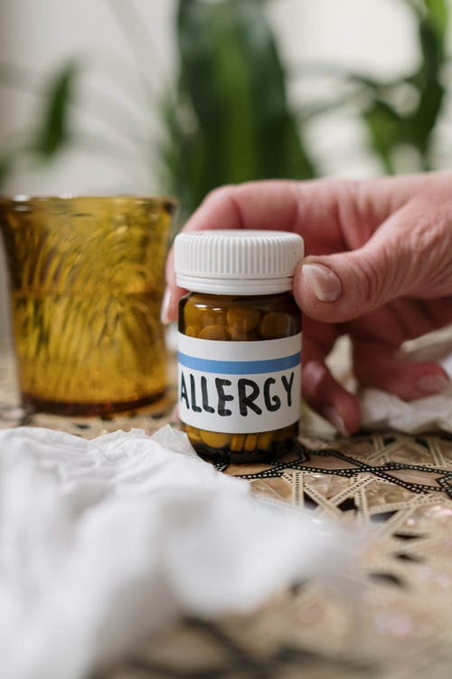 Person Holding Allergy Medicine Bottle