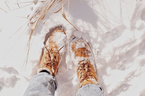 Person in Brown Work Boots Standing on Snow Covered Ground