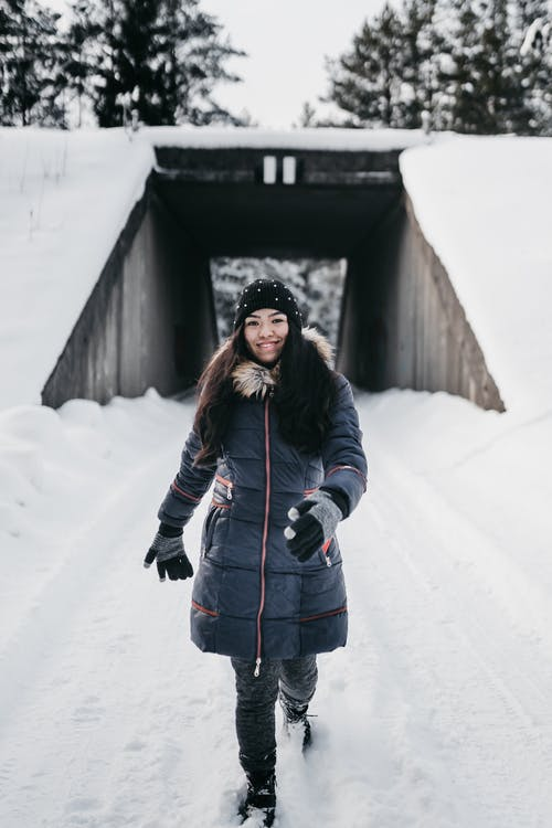 Smiling ethnic female in warm outerwear walking on snowy path