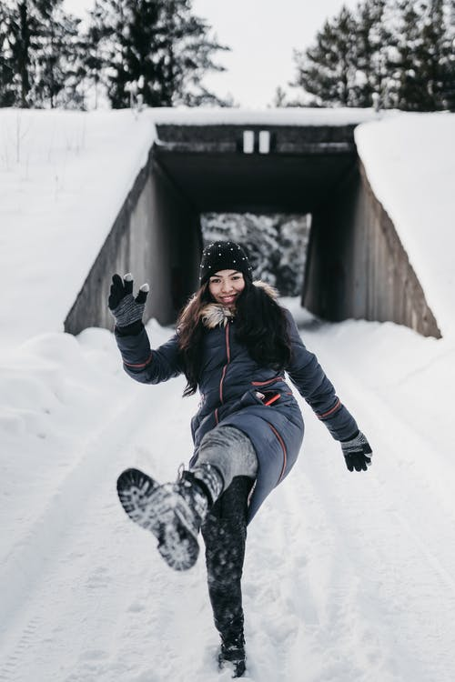 Full body of excited female wearing winter outerwear kicking snowdrift standing against wooden bridge and evergreen trees