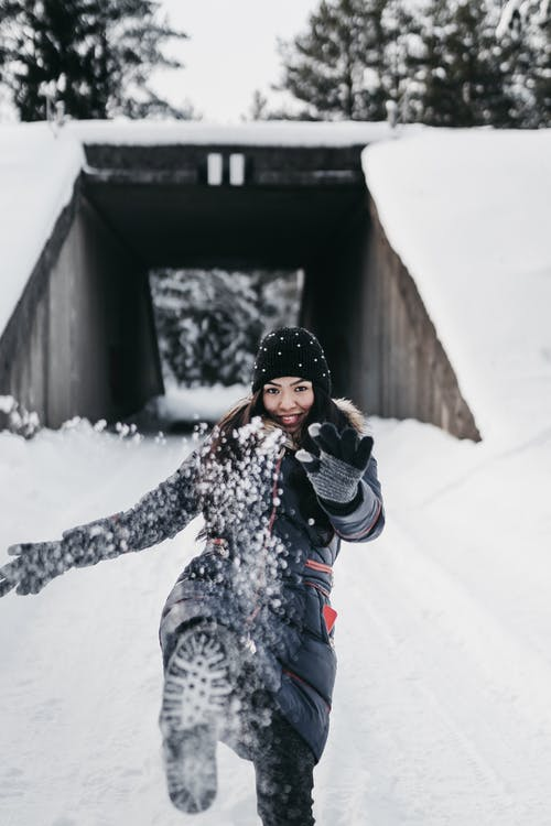 Playful woman having fun in snowy park