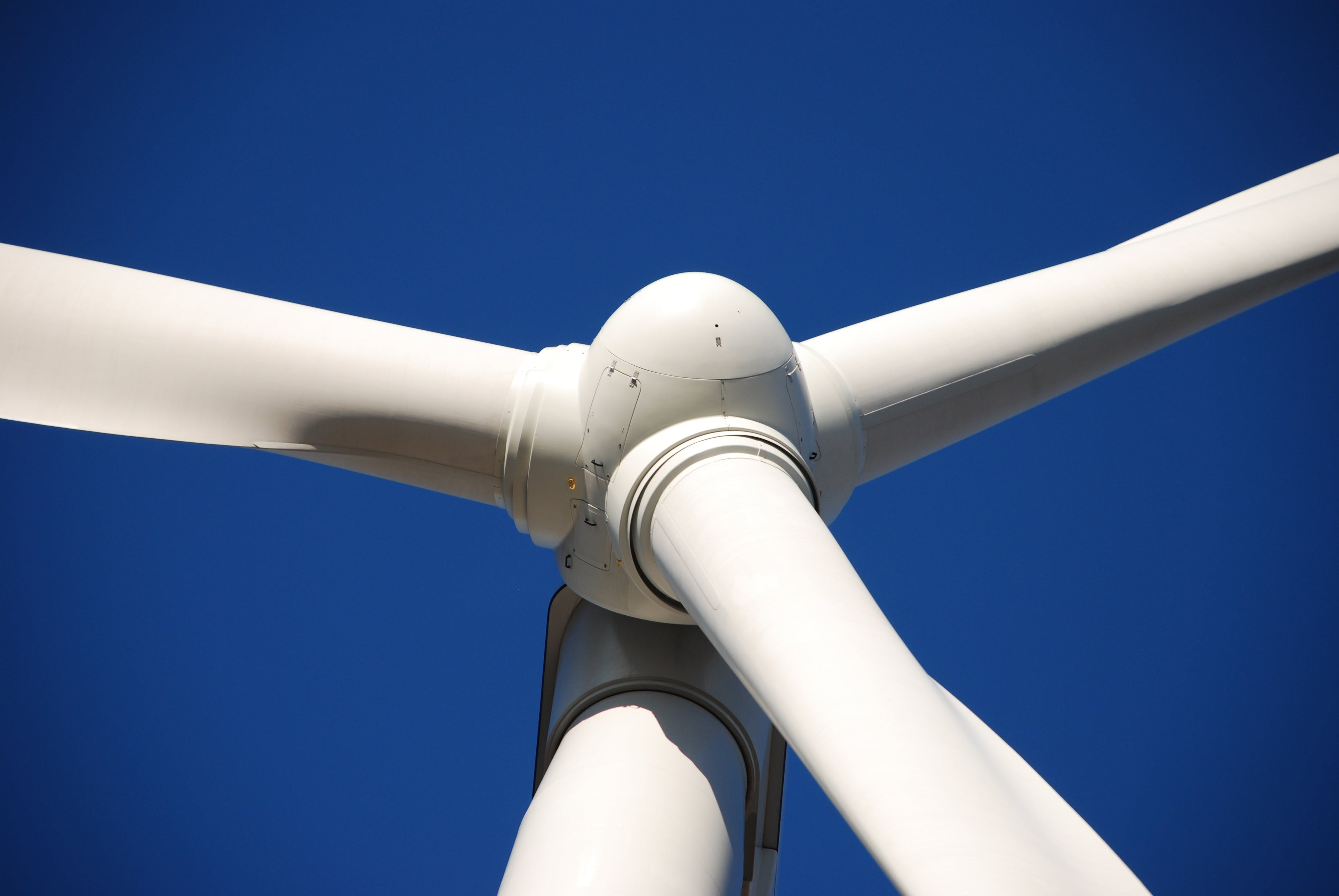 Low Angle Photo of White Wind Turbine Under Deep Blue Sky