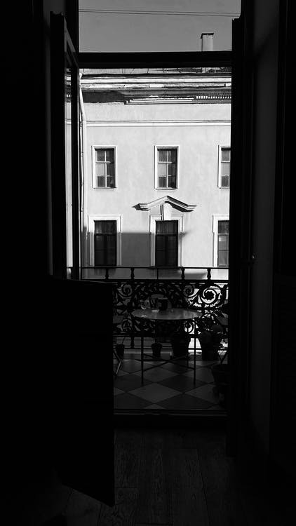 Black and white from dark room view of round table on small balcony against apartment building in town