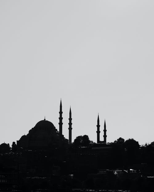Black and white silhouette of mosque with minarets located in Muslim town against clear sky