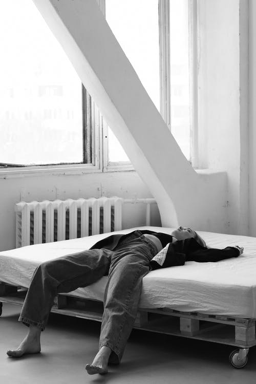 Grayscale Photo of Man Lying on Bed