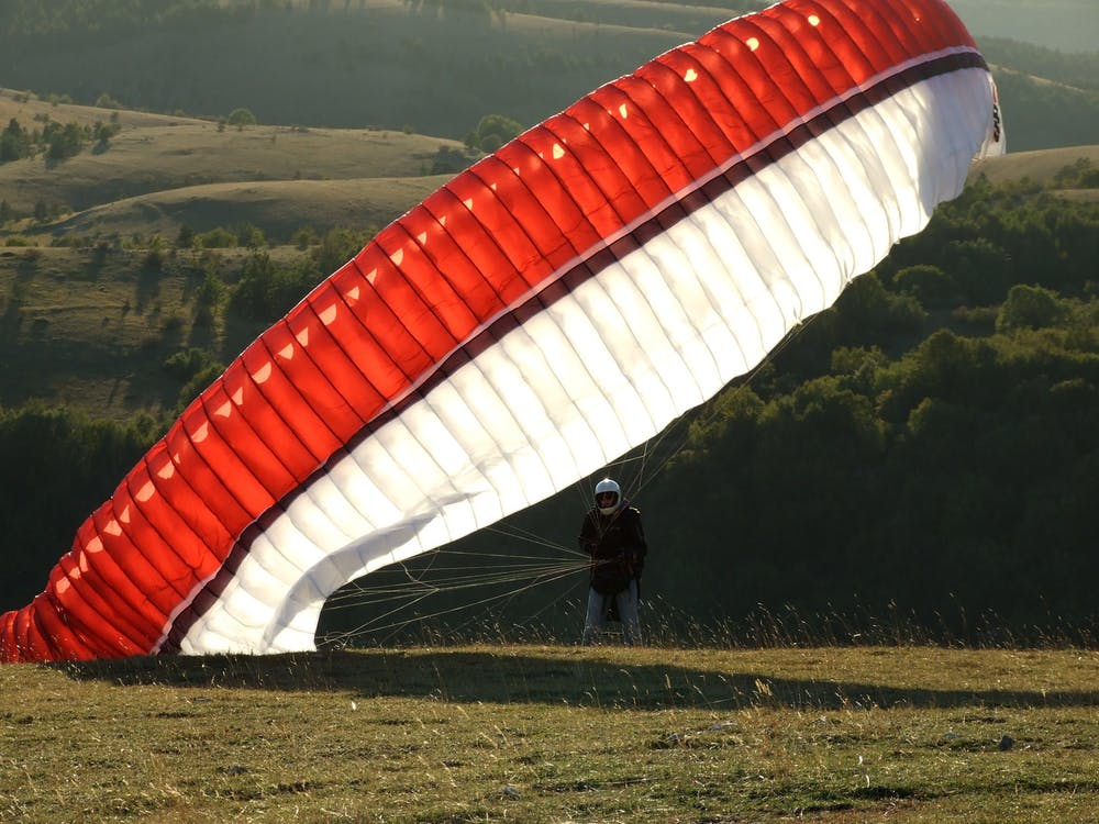 Man on the Ground With a Red Black and White Parachute