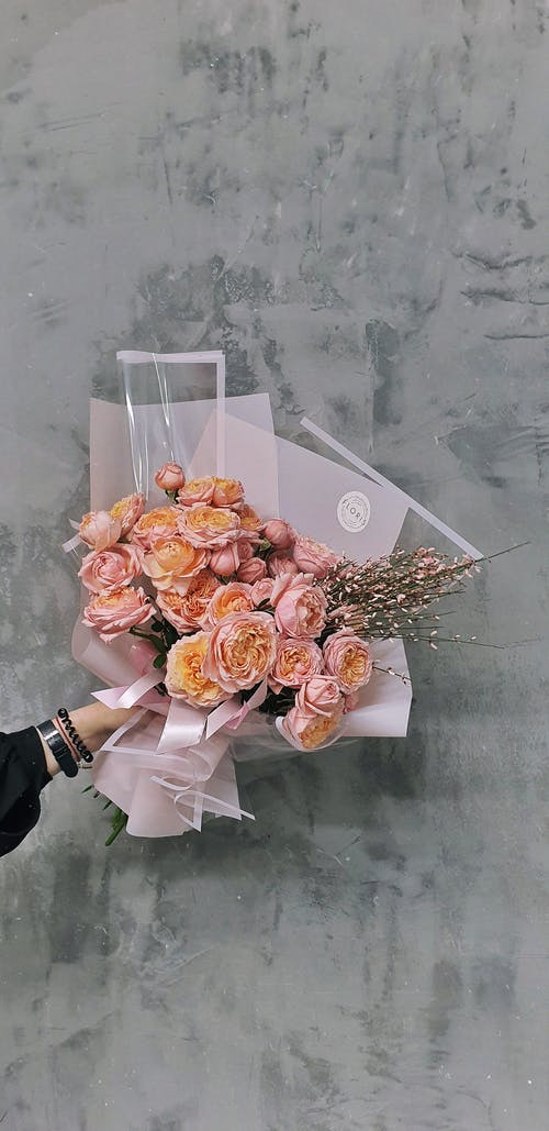 Crop unrecognizable female florist demonstrating elegant bouquet of fresh Austin roses wrapped in rose and transparent papers against gray wall