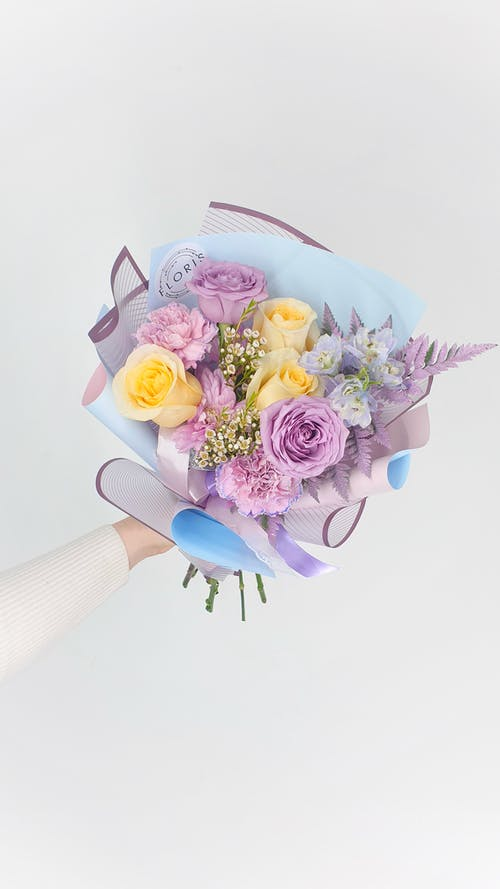Crop unrecognizable florist demonstrating bunch of roses with decorative sprigs in wrapping paper tied with ribbon on white background