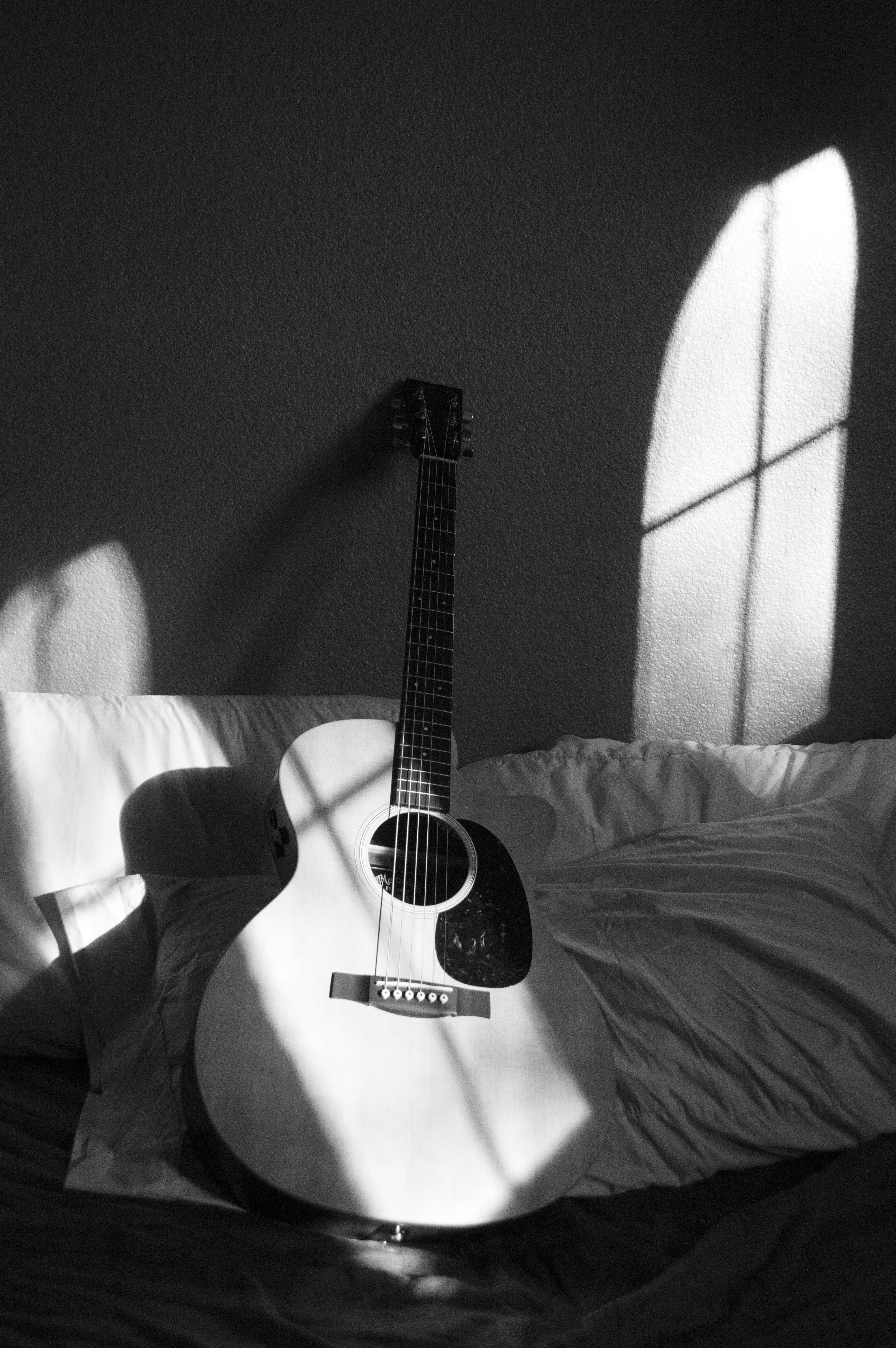 White Acoustic Guitar on Grey and White Textile