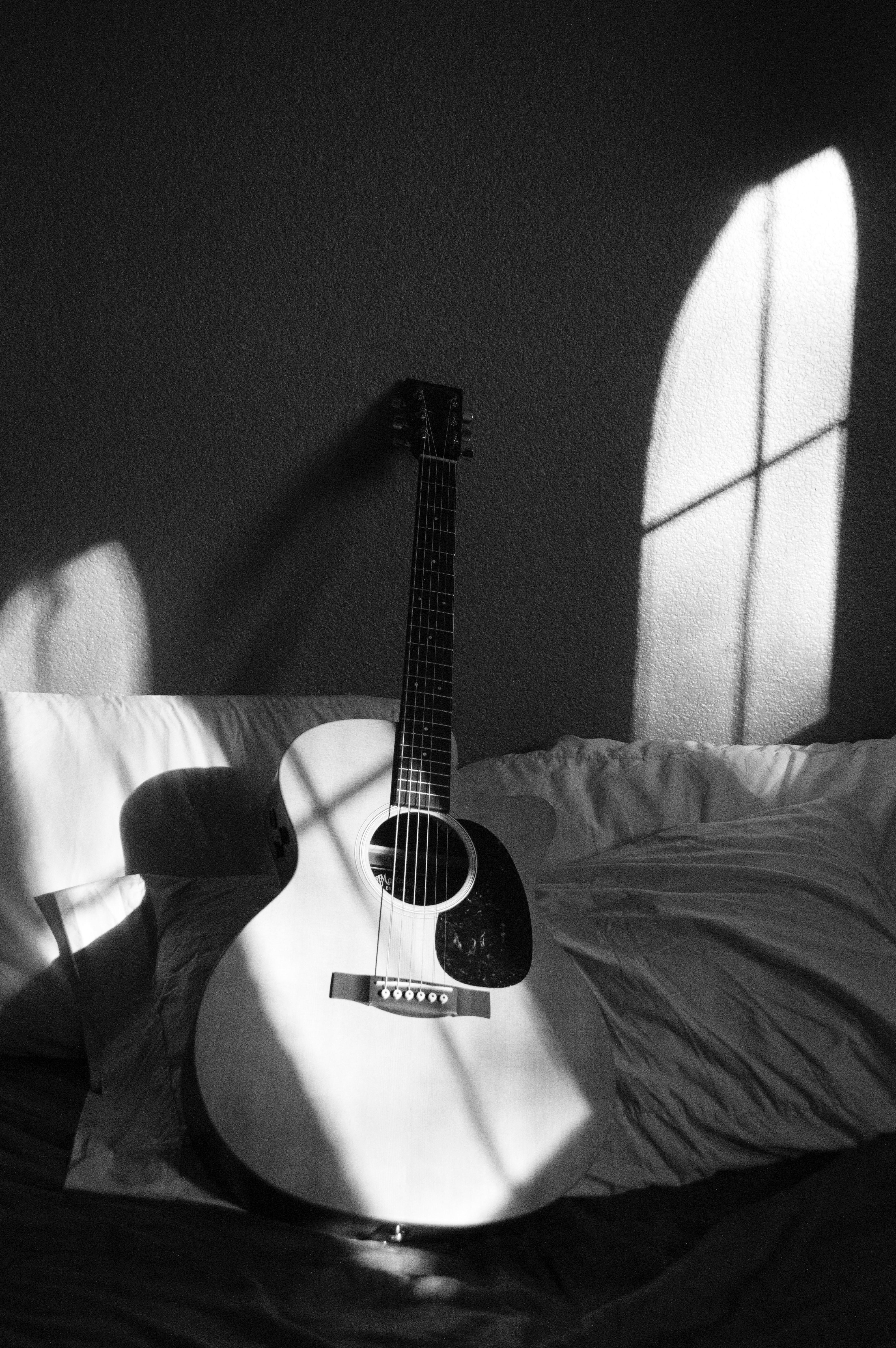 White Acoustic Guitar On Grey And White Textile Free Stock Photo