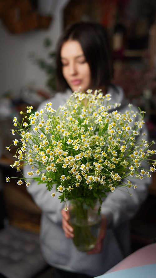 Female florist standing with blooming chamomiles in glass vase with water in floral workshop