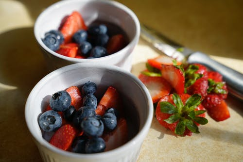 Bowls of ripe delicious strawberries and blueberries served on table
