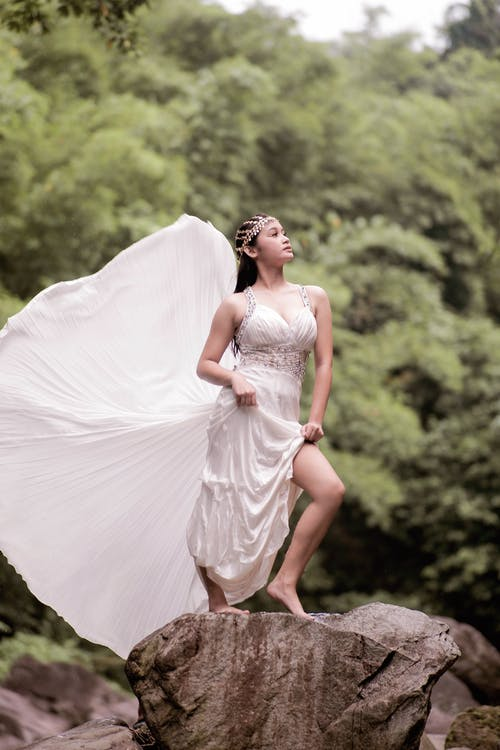 Woman in White Wedding Dress Standing on Brown Rock