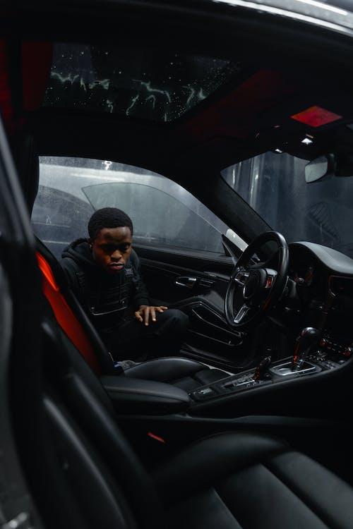 Man in Black Jacket Sitting on Car Seat