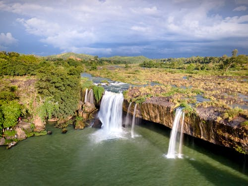 Waterfalls on Green Grass Field