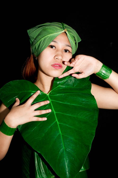 Woman in Green Shirt Holding Green Leaf
