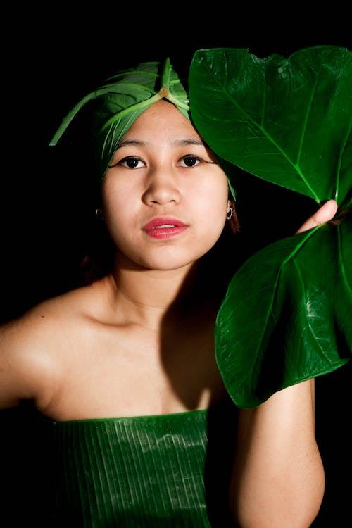 Woman in Green Tube Dress Holding Green Leaves