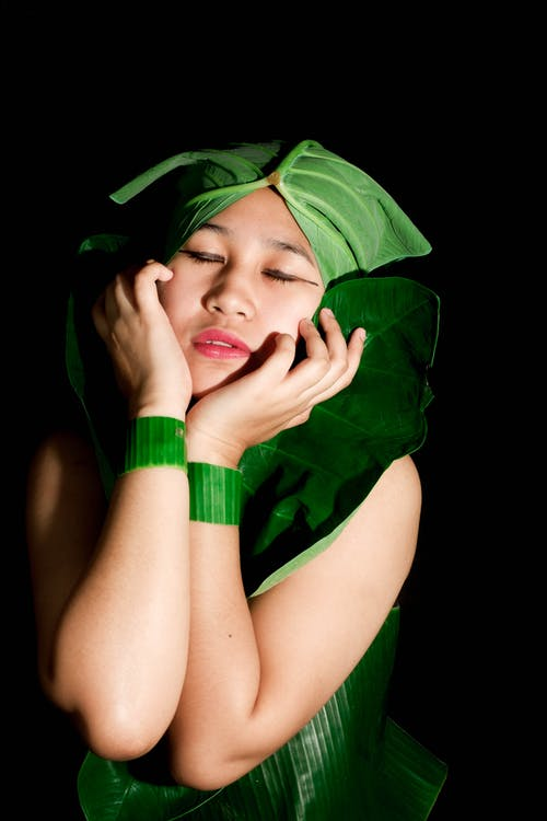 Woman in Green Long Sleeve Shirt Covering Her Face With Her Hands