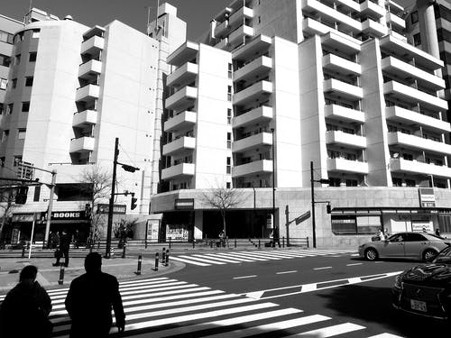 Grayscale Photo of Man Walking on Pedestrian Lane Near Building