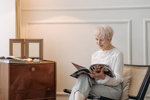 An Elderly Woman Reading a Magazine