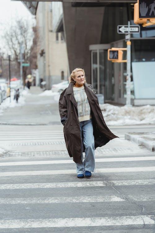 Elderly woman in coat crossing road in town
