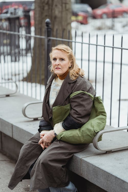 Amazed woman resting on bench in city