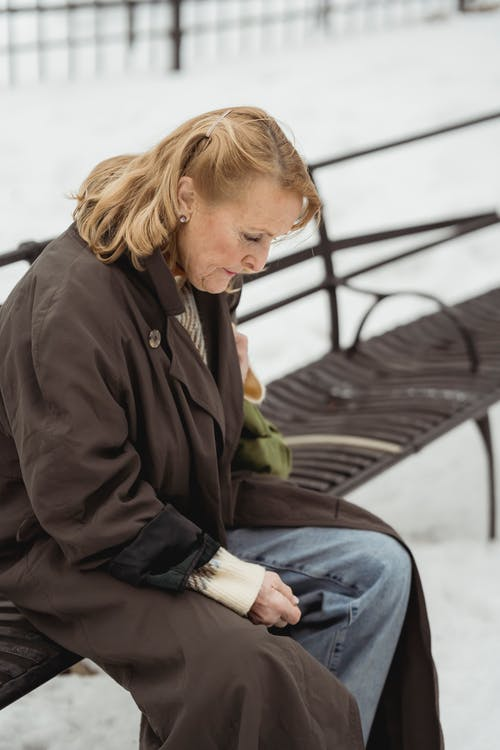Side view of hopeless senior female in outerwear looking down while sitting on bench in winter city