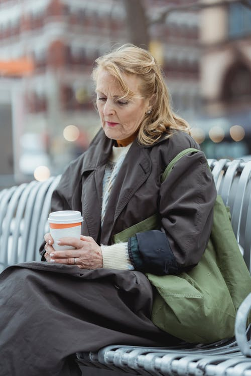 Melancholic female in coat with bag and takeaway hot drink sitting on bench in city